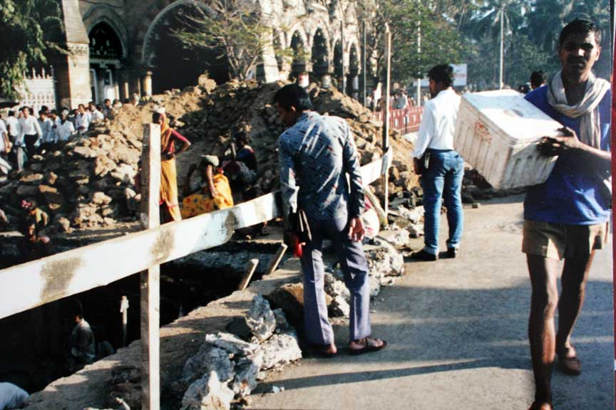 Women carrying dirt out  of a large hole, Mumbai